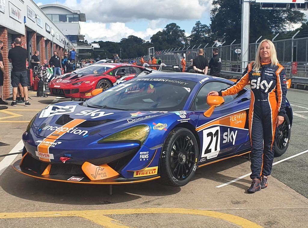 Mia Flewitt stands next to the distinctive blue and orange Balfe Motorsport McLaren 570s GT4