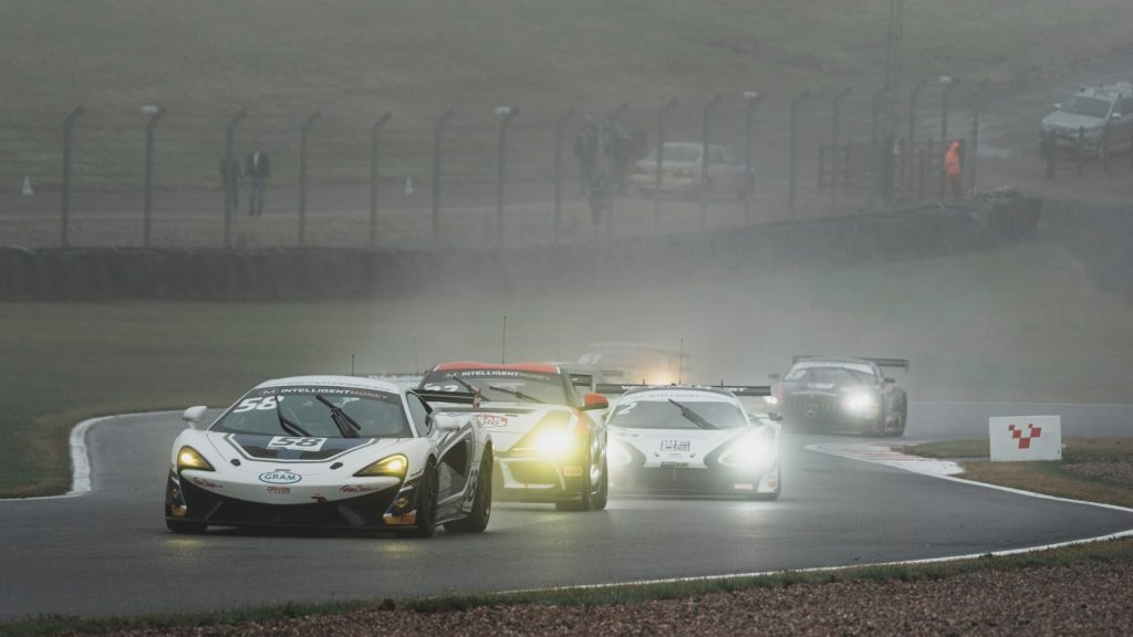 A HHC Motorsport McLaren leads a pack of GT4 cars at Old Hairpin on the Donington Park GP circuit.