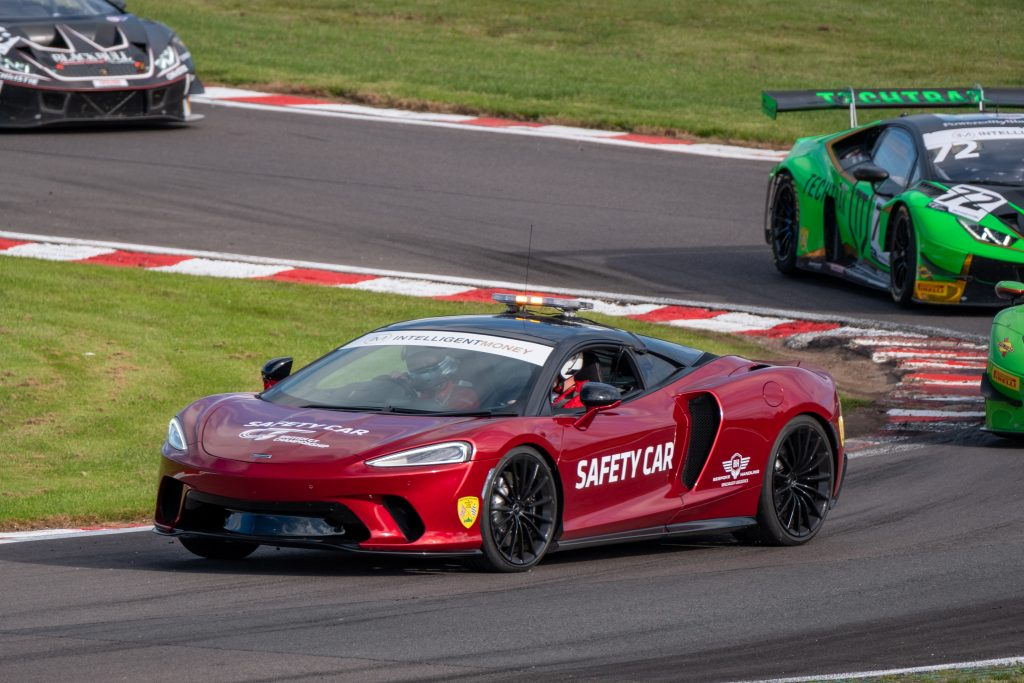 The red McLaren GT Safety car is leading other cars around Oulton Park